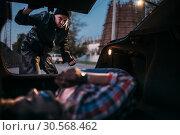 Serial maniac looks on female victim in car trunk. Стоковое фото, фотограф Tryapitsyn Sergiy / Фотобанк Лори