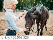Купить «Young blonde woman take caring for brown horse», фото № 30568526, снято 17 сентября 2017 г. (c) Tryapitsyn Sergiy / Фотобанк Лори