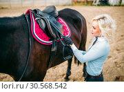 Купить «Female rider preparing a horse saddle,», фото № 30568542, снято 17 сентября 2017 г. (c) Tryapitsyn Sergiy / Фотобанк Лори