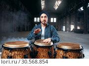 Купить «Male drummer plays on wooden drum», фото № 30568854, снято 26 октября 2017 г. (c) Tryapitsyn Sergiy / Фотобанк Лори