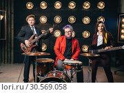 Купить «Musical group in suits on the stage with lights», фото № 30569058, снято 10 ноября 2017 г. (c) Tryapitsyn Sergiy / Фотобанк Лори
