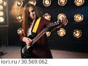 Купить «Female musician in suit playing on electric guitar», фото № 30569062, снято 10 ноября 2017 г. (c) Tryapitsyn Sergiy / Фотобанк Лори