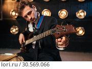 Купить «Rock guitarist in suit playing on bas-guitar», фото № 30569066, снято 10 ноября 2017 г. (c) Tryapitsyn Sergiy / Фотобанк Лори