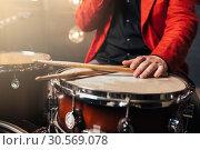 Male drummer in red suit sitting behind drum set. Стоковое фото, фотограф Tryapitsyn Sergiy / Фотобанк Лори
