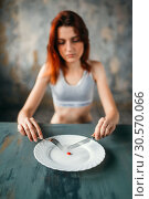 Купить «Woman against plate with a tablet for weight loss», фото № 30570066, снято 10 января 2018 г. (c) Tryapitsyn Sergiy / Фотобанк Лори