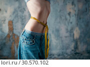 Купить «Thin woman in jeans measures waist, weight loss», фото № 30570102, снято 10 января 2018 г. (c) Tryapitsyn Sergiy / Фотобанк Лори