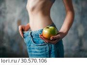 Купить «Woman with apple in hand tries on big size jeans», фото № 30570106, снято 10 января 2018 г. (c) Tryapitsyn Sergiy / Фотобанк Лори