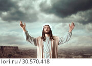 Jesus praying with his hands up against cloudy sky. Стоковое фото, фотограф Tryapitsyn Sergiy / Фотобанк Лори