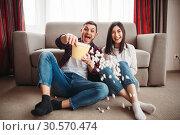 Купить «Laughing couple watch comedy movie with popcorn», фото № 30570474, снято 11 февраля 2018 г. (c) Tryapitsyn Sergiy / Фотобанк Лори