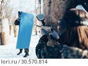 Купить «Paintball player shooting at enemy with the shield», фото № 30570814, снято 25 февраля 2018 г. (c) Tryapitsyn Sergiy / Фотобанк Лори