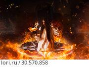 Купить «Woman sitting in burning pentagram circle, magic», фото № 30570858, снято 27 февраля 2018 г. (c) Tryapitsyn Sergiy / Фотобанк Лори