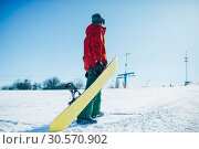 Купить «Snowboarder in glasses poses with board in hands», фото № 30570902, снято 6 марта 2018 г. (c) Tryapitsyn Sergiy / Фотобанк Лори
