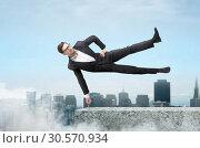 Купить «Businessman easily hangs on one finger», фото № 30570934, снято 10 марта 2018 г. (c) Tryapitsyn Sergiy / Фотобанк Лори