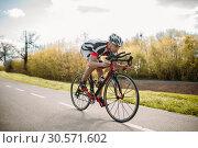 Купить «Male cyclist rides on bicycle, front view», фото № 30571602, снято 28 апреля 2018 г. (c) Tryapitsyn Sergiy / Фотобанк Лори