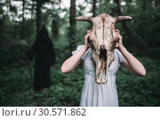 Victim and death in a black hoodie and with scythe. Стоковое фото, фотограф Tryapitsyn Sergiy / Фотобанк Лори