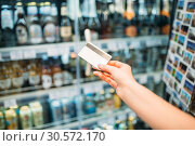 Купить «Female hand with credit card, alcohol market», фото № 30572170, снято 31 мая 2018 г. (c) Tryapitsyn Sergiy / Фотобанк Лори