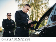 Купить «Male police officers check vehicle on the road», фото № 30572298, снято 6 июня 2018 г. (c) Tryapitsyn Sergiy / Фотобанк Лори