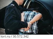 Купить «Police officer put the intruder into the car», фото № 30572342, снято 6 июня 2018 г. (c) Tryapitsyn Sergiy / Фотобанк Лори