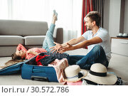 Купить «Young couple packing their suitcases for vacation», фото № 30572786, снято 30 июня 2018 г. (c) Tryapitsyn Sergiy / Фотобанк Лори