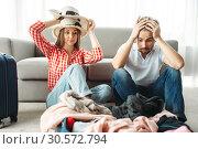Купить «Tired couple packing overloaded bag for vacation», фото № 30572794, снято 30 июня 2018 г. (c) Tryapitsyn Sergiy / Фотобанк Лори