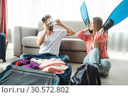 Young couple packing their baggage for vacation. Стоковое фото, фотограф Tryapitsyn Sergiy / Фотобанк Лори