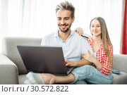 Купить «Couple looks on laptop screen, fees on vacation», фото № 30572822, снято 30 июня 2018 г. (c) Tryapitsyn Sergiy / Фотобанк Лори