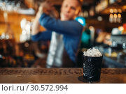 Купить «Black glass full of ice stands on bar counter», фото № 30572994, снято 6 июля 2018 г. (c) Tryapitsyn Sergiy / Фотобанк Лори