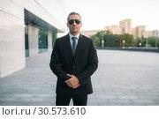 Купить «Male bodyguard in suit, earpiece and sunglasses», фото № 30573610, снято 8 августа 2018 г. (c) Tryapitsyn Sergiy / Фотобанк Лори