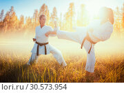 Купить «Two female karate in kimono fight in summer field», фото № 30573954, снято 26 августа 2018 г. (c) Tryapitsyn Sergiy / Фотобанк Лори