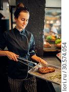 Купить «Female cook holds prepared steak, grilled bbq meat», фото № 30574054, снято 27 августа 2018 г. (c) Tryapitsyn Sergiy / Фотобанк Лори