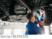 Mechanic with lamp checks car brake hoses. Стоковое фото, фотограф Tryapitsyn Sergiy / Фотобанк Лори