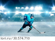 Купить «One hockey player skating with stick on ice arena», фото № 30574710, снято 20 апреля 2017 г. (c) Tryapitsyn Sergiy / Фотобанк Лори