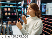 Female customer testing lip liner in makeup shop. Стоковое фото, фотограф Tryapitsyn Sergiy / Фотобанк Лори