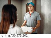 Купить «Female customer signs order to pizza delivery boy», фото № 30575262, снято 4 ноября 2018 г. (c) Tryapitsyn Sergiy / Фотобанк Лори