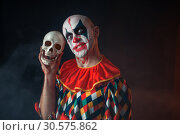 Bloody clown with crazy face holds human skull. Стоковое фото, фотограф Tryapitsyn Sergiy / Фотобанк Лори
