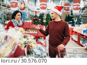Couple buying Christmas souvenirs in supermarket. Стоковое фото, фотограф Tryapitsyn Sergiy / Фотобанк Лори
