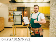 Купить «Worker holds repair checklist against refrigerator», фото № 30576782, снято 28 февраля 2019 г. (c) Tryapitsyn Sergiy / Фотобанк Лори