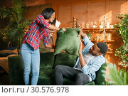 Black couple having fun on sofa, pillow fight. Стоковое фото, фотограф Tryapitsyn Sergiy / Фотобанк Лори