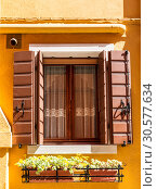 A window with open shutters and flowers in a drawer underneath. A house on Burano island, Venice, Italy (2017 год). Стоковое фото, фотограф Наталья Волкова / Фотобанк Лори