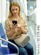 Купить «Nice girl speaks on the mobile phone in the subway train», фото № 30578446, снято 31 марта 2019 г. (c) Яков Филимонов / Фотобанк Лори