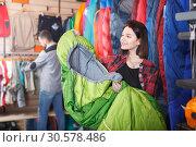 Купить «Ordinary female customer examining sleeping bags», фото № 30578486, снято 8 марта 2017 г. (c) Яков Филимонов / Фотобанк Лори