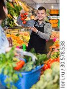 Купить «Male seller assisting in buying», фото № 30578538, снято 18 марта 2017 г. (c) Яков Филимонов / Фотобанк Лори