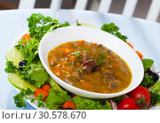 Купить «Delicious cooked goulash from chicken hearts served with vegetables», фото № 30578670, снято 22 апреля 2019 г. (c) Яков Филимонов / Фотобанк Лори