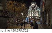 Купить «People walking in the street overlooking Metropolis Building. Night Madrid», видеоролик № 30579702, снято 17 января 2018 г. (c) Данил Руденко / Фотобанк Лори