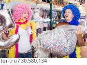 Купить «Laughing girl and guy are staying with large bagful of confetti», фото № 30580134, снято 11 апреля 2017 г. (c) Яков Филимонов / Фотобанк Лори