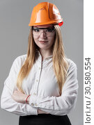 Portrait of a young attractive woman with blond hair in orange helmet on a neutral gray background. Стоковое фото, фотограф bashta / Фотобанк Лори