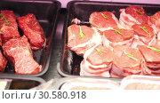Купить «Pieces of tenderloin fresh raw beef meat with rosemary, pork and slices of bacon are lying in black trays on the store shelf ready for sale in slow mo camera motion 4K video with no people», видеоролик № 30580918, снято 5 ноября 2018 г. (c) Uladzimir Sitkouski / Фотобанк Лори