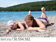 Купить «Мать с дочерью загорают на пляже, лежа на гальке возле моря», фото № 30594582, снято 3 июня 2016 г. (c) Кекяляйнен Андрей / Фотобанк Лори