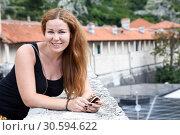 Купить «Портрет улыбающейся привлекательной женщины на фоне стен древней крепости», фото № 30594622, снято 2 июня 2016 г. (c) Кекяляйнен Андрей / Фотобанк Лори