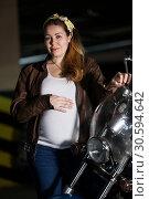 Купить «Портрет беременной женщины, одетой в коричневую кожаную куртку, стоящей перед фарой мотоцикла и держащей свой большой живот», фото № 30594642, снято 24 февраля 2019 г. (c) Кекяляйнен Андрей / Фотобанк Лори